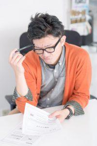 自動車免許の住所変更に必要な書類を書く男性
